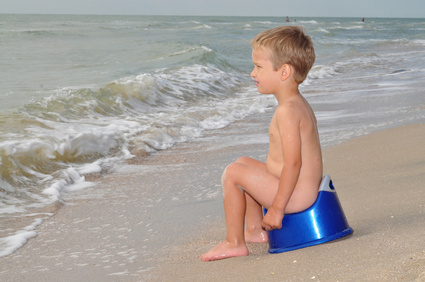 Boy sitting on a potty on the seashore
